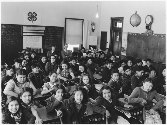 Classroom with students and teachers. License: Public Domain